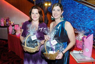 President Nicole Wilson, left, and Vice-President Taia Younis of Simplifying Lives, for a cause hold gift baskets at their Vapor fundraiser. Ed Burke 8/30/12
