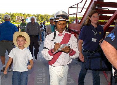 Seven year old Bradley Brophy of Greenwich gets an autograph from jockey Rajiv Maragh after his winning ride aboard Miami Cat in Thursday's The Equalize 9th race feature. Ed Burke 8/30/12