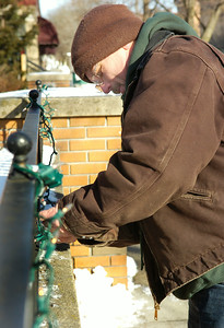 Saratoga Downtowner employee  John Gamble, of Saratoga Springs, restrings lights onto their walls for the Holiday season in the blistering cold Tuesday morning. Photo Erica Miller 12/29/09 news_ColdWeather1_Wed