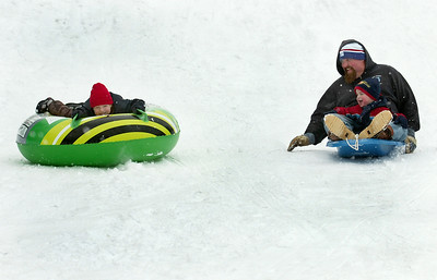 Chris Comstock, 4 years old, slides down the hill on his green sled wit his father Kenny and younger brother James, 2, at the McGregor Links Golf Course hill in Wilton after a fresh snow fall Monday morning. Photo Erica Miller 12/28/09 news_SledSnow_Tues