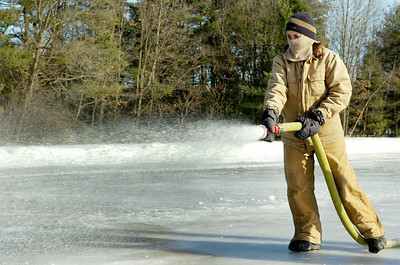 NYS Park worker Devon Sherman coats the ice rank near the Warming Hut at the Saratoga Spa Park Tuesday morning in the shivering cold hoping to perfect the ice for hockey games. Photo Erica Miller 12/29/09 news_ColdWeather2_Wed