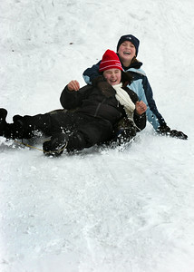 Vaughn O'Conner, 12 of Greenfield, and friend Sasha Weilbaker, 12 of Wilton, slide down the hill after falling off their sled at the McGregor Links Golf Course hill in Wilton after a fresh snow fall Monday morning. Photo Erica Miller 12/28/09 wg_SledSnow2