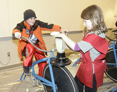 Eleven year old Jordan Audi on Wynantskill pedals hard to mix fender blender lemonade during First Night at Saratoga Springs City Center. First Night volunteer Zoe Beitzel, age 10, helps steady the blender. Ed Burke 12/31/10