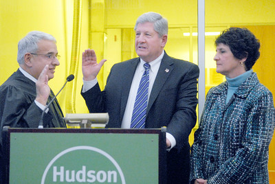 Senator Roy McDonald raises his hand as Honorable Stephen A. Ferradino, Saratoga County Supreme Court Justice, swears him into office beside his wife Angela Wednesday afternoon at the TEC-SMART campus, through Hudson Valley Community College. Photo Erica Miller 12/29/10 news_McDonald1_Thurs
