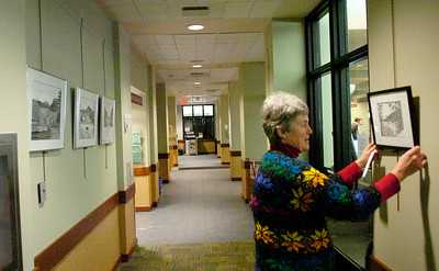 Pen and ink artist Mary Ellen Lincourt of Day hangs her original works Tuesday in the hallway at Saratoga Springs Public Library. The display will be up for the month of January as part of the Saratoga Arts Art in Public Places program. Ed Burke 12/28/10