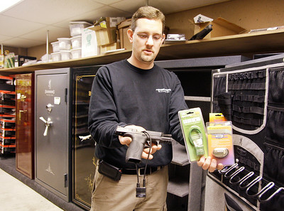 Kevin Zacharewicz, owner of Zack's Sports on Rt. 9 in Malta holds gun and trigger locks he sells at his store which specializes in guns and ammunition. Behind are several models of gun safes he sells to safely store firearms. Ed Burke 12/31/10