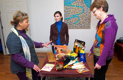 Standing near a table filled with items symbolic of the holiday, artist Francelise Dawkins explains the history and meaning of Kwanzaa to Danica Lichtig, center, and Wendy Wood Ordway during a Kwanzaa party Friday at Feenex Center and Gallery on Beekman St. Ed Burke 12/30/11