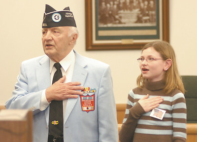 Brianna Collins helps Gene Corsale lead people in the Pledge of Allegiance during the monthly deceased veteran ceremony at the County Board of Supervisors building Tuesday in Ballston Spa. Brianna's great-grandfather, World War II veteran Clifford Palmateer of Galway was honored during the ceremony. Corsale is Co-Charirman of the county's Honor a Deceased Veteran Ceremony. Ed Burke 2/23/10
