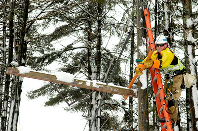 High up on a ladder, Jim Zeigler with National Grid places safety rubber onto the electric wires on North Creek Road (County Road 19) in Porter Corners, in restoration of the pole. Due to heavy snow, many branches and limbs fell in the Town of Greenfield. Photo Erica Miller 2/24/10 news_NatGrid1_Thurs