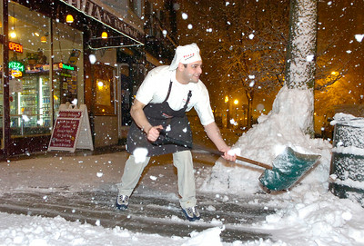 A heavy wet snow falls on Michael Calvi  as he shovels the sidewalk Tuesday evening in front of Pizza on Broadway, the restaurant owned by his family. Ed Burke 2/13/10