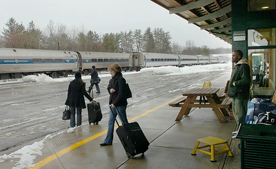 Passengers head to Amtrak's on-time New York City-bound Adirondack train Wednesday at the Saratoga Springs Train Station. Running about 4 hours late due to weather related delays, the Montreal-bound train can be seen on the closer track waiting for the mainline to clear so it can continue its journey north. Ed Burke 2/24/10
