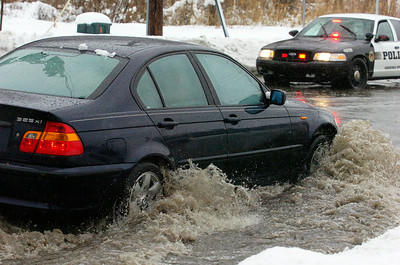 A car drives through the intersection of East Avenue and Excelsior Avenue as rain hits Saratoga area melting snow and flooding streets and streams.  Photo Erica Miller 2/28/11 news_Flooding2_Tues