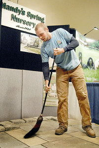 Manager at Mandy's Springs Nursery Shane Sullivan sweeps their booth for the annual Saratoga Springs Rotary Home Show at the Saratoga City Center for a weekend event, the Nursery owned by Todd Smith has attend every year since it has started. Photo Erica Miller 2/25/11 news_SetupRotary2_Sat