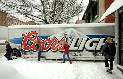 Pedestrians walk around a beer delivery truck Friday which got stuck in the snow trying to enter Gardner Lane between Lillian's Restaurant and N. Fox Jewelers. Ed Burke 2/25/11