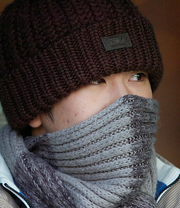 Jay Jay Fang, a junior at Skidmore College, protects himself from Friday's cold and wind as he waits for a bus on Broadway to take him back to campus. Ed Burke 1/29/10