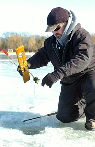 Kevin Charbonneau, of Quaker Springs, checks his tip-up line while ice-fishing with friend Don Parker on Saratoga Lake in the chilly temperatures Friday morning. Both are volunteers with the Quaker Springs Fire Department that will be holding live drills of ice water rescues from 8 a.m. to noon on the lake today on the docks off Route 9P across from the State Boat Launch. There will be twelve people in jumpsuits, including South Glens Falls and Monroe Fire Departments, using ropes and baskets. Photo Erica Miller 1/29/10 news_Fishman_Sat