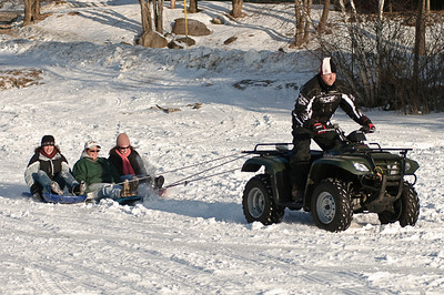 Showing that sledding isn't just for kids, Rick Lisieski pulls Blair Sass, Georgie Reed and Mechelle Fisher across the ice on Lake Desolation after the outhouse races Sunday afternoon. Photo Eric Jenks 1/31/10