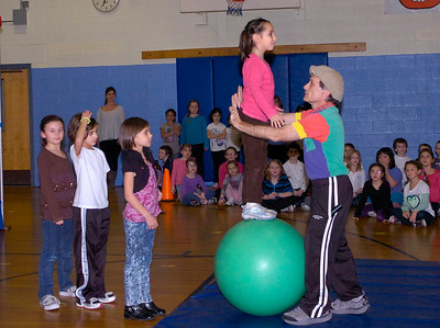 Caroline Street Elementary School second grader Naomi Chavez balances on a ball as Rick Davis of Circus Smirkus stands by during Friday night's performance by second graders at the school. The performance was the culmination of a week-long workshop by Davis with the students to build teamwork, self-esteem and to sharpen their powers of observation. Ed Burke 1/27/12
