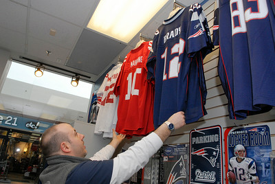 General Manager at The Stadium, located inside the Wilton Mall near Old Navy, Wayne Frankey organizes some of his Giants and Patriots nick-nacks in their store for the upcoming Superbowl this Sunday. Photo Erica Miller 1/30/12 news_Superbowl2_Tues