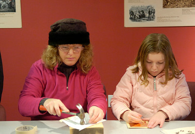 Allison Wendling and daughter Abagail of Queensbury try their hands at tin piercing and copper embossing during Saturday's Frost Faire at Saratoga National Battlefield. Ed Burke 1/28/12