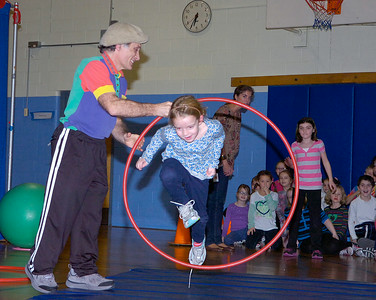 Caroline Street Elementary School second grader Maddie Ide jumps through a hoop held by Rick Davis of Circus Smirkus during Friday night's performance by second graders at the school. The performance was the culmination of a week-long workshop by Davis with the students to build teamwork, self-esteem and to sharpen their powers of observation. Ed Burke 1/27/12