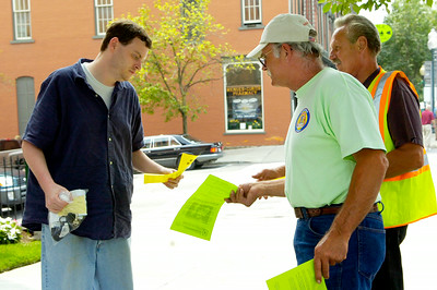 While strolling down Broadway, Kevin Savard of Saratoga Springs takes one of the flyers from Chuck Martin of Amsterdam (front) and Art Seacord of Niskayuna. Both employees are trying to make Bette & Cring Construction Group to pay the areas standard wages and benefits to their carpenters for the work done at 38 High Rock Ave. Photo Erica Miller 7/23/09 news_CarpWages_Fri