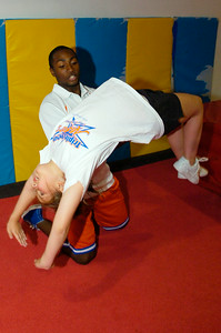 Gym manager Jahmere Holland, coach at Albany High, helps teach Gianna Costanzo, 10 years old, her back hand spring Monday evening at the Stepping Stars gymnastics and dance studio. Photo Erica Miller 7/20/09 news_TripleThreat2_Tues