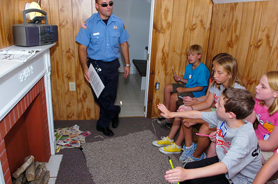 Students point out different hazards that may cause a fire to fireman Bret Carpenter on the fire bus in the fake living room, along with the kitchen where they then simulate a fire where the students have to safely evacuate. The program uses the D.A.R.E. curriculum with the Saratoga partnership for prevention and community coalition, which is supported by the prevention council including parents and the schools. All students throughout the four weeks are becoming 6th graders this year.  The program teaches the students how to be a good citizen, decision making, consequences, good reputations and drug violence. Photo Erica Miller 7/20/09 news_DAREprog3_Tues