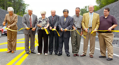 Regional Directory for DOT 1 Mary  Ivey, Town of Malta Supervisor Paul Sausville, Mayor of Round Lake Dixie Lee Sacks, Town of Wilton Supervisor Art Johnson, DOT 1 Acting Commissioner Stanley Gee, State Assemblyman Tony Jordan, VP and General Manager of Global Foundries Norm Armour, and Town of Stillwater supervisor Shawn Connelly cut the ribbon opening of the Round Lake Bypass in the village of Round Lake and town of Malta Tuesday morning. Photo Erica Miller 7/21/09 news_Bypass1_Wed