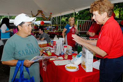 Backstretch Employee Betty Hernandez listens as Sandy Russell, B.E.S.T. volunteer with the Cornell Cooperative, explains the importance of breakfast in the morning and milk at the Backstretch employee health fair. Photo Erica Miller 8/2/11 news_HealthFair1_Wed