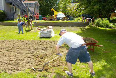 Don Little, director of the veterans shelter at 36 Church St. in Ballston Spa, collects sod from a new garden area to place near a retaining wall being built by Lowe's employees behind. The employee volunteers from Lowe's also contructed a new storage shed and removed the old one. Next spring the garden seen at back right will be replanted in the new location. Ed Burke 7/30/11