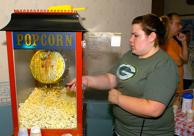 Maplewood manor Leisure Aide Kaylee Niles makes popcorn during Thursday's Car Cruise night. Ed Burke 7/26/12