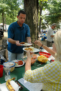 Jim Bieland, from Columbia Maryland (and Bethel NY) helped by Barbara Busch, from Oakdale NY, served up a plate of food for their favorite betting teller at the Saratoga Race Course. Photo Erica Miller 7/30/12 news_FoodTrack2_Tues