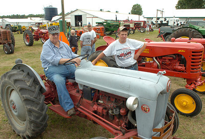 John Wojtowicz of Clifton Park stands nearby as Ed Zuzick of Stillwater sits aboard his 1954 Ford tractor during the weekend Antique Tractor Show at the Washington County Fairgrounds. Ed Burke 7/28/12
