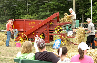 An early 1900s thresher seperates oat grains from stalks during a demonstration Saturday at the Antique Tractor Show at the Washington County Fairgrounds. Ed Burke 7/28/12