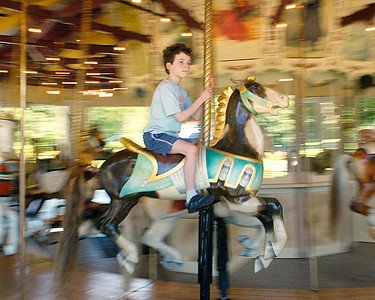 Seven year old Skyler Friedman of Delmar rides the carousel in Congress Park Thursday. Ed Burke 6/30/11
