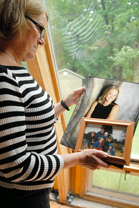 Anne Kauth holds a photograph of her daughter Cecelia, now 25 year-old, and a family portrait of her late ex-husband. Cecelia will be riding a bike from Oregon to NYC arriving to the city on September 11th to commemorate her father's passing, who was killed on 9/11.Photo Erica Miller 6/29/11 news_KauthBike1_up