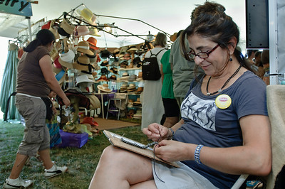 Tina Accardi works on a piece of Jewlery in the market section of the 35th annual Freihofer's Jazz Festival Sunday afternoon. Photo Eric Jenks 7/1/12