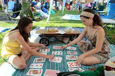 Young teens Emily Irwin, left, and Rachel Stein of Saratoga Springs play a card game call Spit while attending the jazz festival with family. Ed Burke 6/29/13