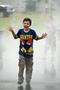Timothy Winslow cools down by a running through mist Sunday afternoon at the Saratoga Fairgrounds during the Family Fun Day event. Photo Eric Jenks 6/30/13