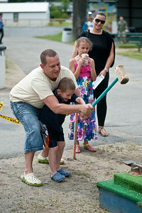 Jeff and Ethan Shein ring the bell with a hammer while Irena (mother) and Kayla Shein watch on at the Saratoga Fairgrounds Sunday afternoon during the Family Fun Day event. Photo Eric Jenks 6/30/13