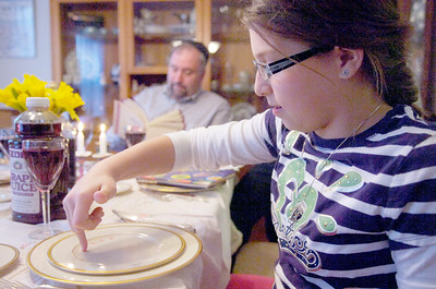 Emily Fisher, 10 years old, dots her plate 10 times in representation of the 10 different plagues during their dinner Monday evening in celebration of Passover with her parents Steve and Robin. Photo Erica Miller 3/29/10 news_FisherFam2_Tues