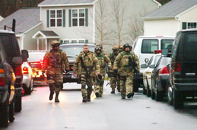 SWAT team heads back to their cars after successfully arresting Aleksander Michaiski after he barricaded himself inside his home on Boylston Street in Glens Falls Tuesday. Photo Erica Miller 3/30/10 news_GFstandoff1_Wed