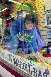 Sandra Capecci sets up a Mardi Gras theme window display at Soave Faire on Broadway in part with the Giving Circle on Tuesday morning. Photo Erica Miller 3/30/10 news_MardiGras2_Wed