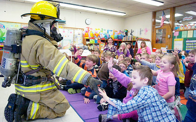 Geared up in his 54 pound suit for a call Saratoga Springs Fireman Matt Avila high-fives Kindergarten students during the Math, Science, Technology Career Fair Day at Division Street Elementary Wednesday morning. Photo Erica Miller 3/31/10 news_CareerFair3_Thurs