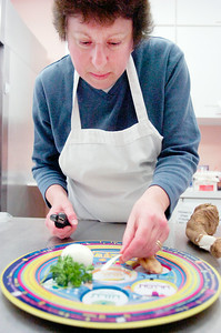 Amy Kantor, of Saratoga Springs, places fresh peels of horseradishes, to represent the bitterness of the experience of Egyptian slavery, onto the Seder Plate which is placed on all the tables. Photo Erica Miller 3/29/10 news_ShaaraTFille2_Tues