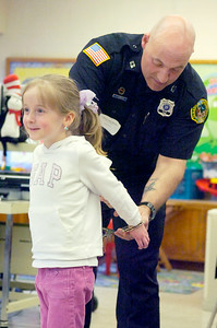 Saratoga Springs Police Office Tony Straus, D.A.R.E. instructor, demonstrates on Mia Fredrick, 5 years old, in her kindergarten class how handcuffs are used during the Math, Science, Technology Career Fair Day at Division Street Elementary Wednesday morning. Photo Erica Miller 3/31/10 news_CareerFair1_Thurs