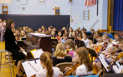 With music director Maura McNamara on piano, Dorothy Nolan Elementary School's 4th and 5th grade orchestra performs in the school gym Wednesday night. Ed Burke 3/30/11