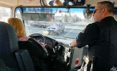 Saratoga Springs bus driver Katie Hensleigh and Saratoga Springs Police Traffic Sergeant Andy Prestigiacomo make their way down Route 9 as they start their route to pick up students to go to Lake Ave Elementary. The Cornell University Cooperative Extension of Saratoga County and the Saratoga Springs Police Department participated Wednesday in Operation Safe Stop Day, a national event during which police officers ride on school buses and follow in marked and unmarked patrol units to crackdown on illegal school bus passing violations. Photo Erica Miller 3/30/11 news_SchoolBus6_Thurs