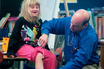 Division Street Elementary School held their annual Math, Science and Technology Career Fair Wednesday. Pediatrician Dr. Emanuel Cirenza MD tests knee reflex on Katherine Lockrow, 8 years old, second grader. Photo Erica Miller 3/30/11 news_CareerFair3_Thurs